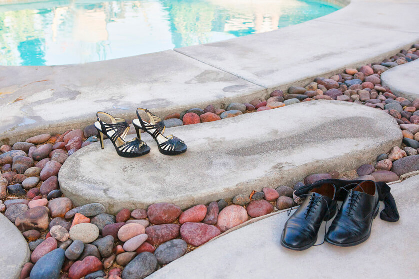 Brides shoes and grooms shoes and socks discarded next to the pool
