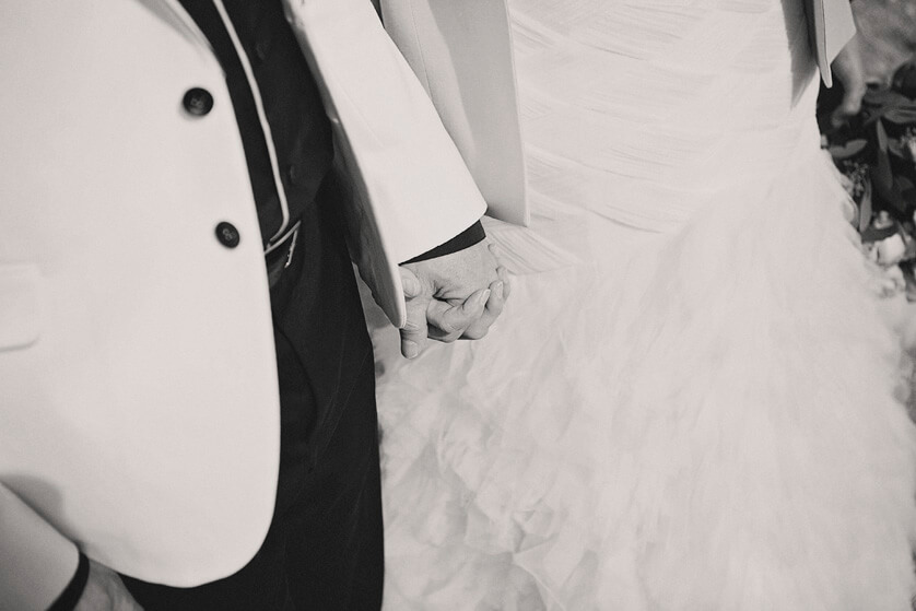 Black and white detail of bride and groom holding hands