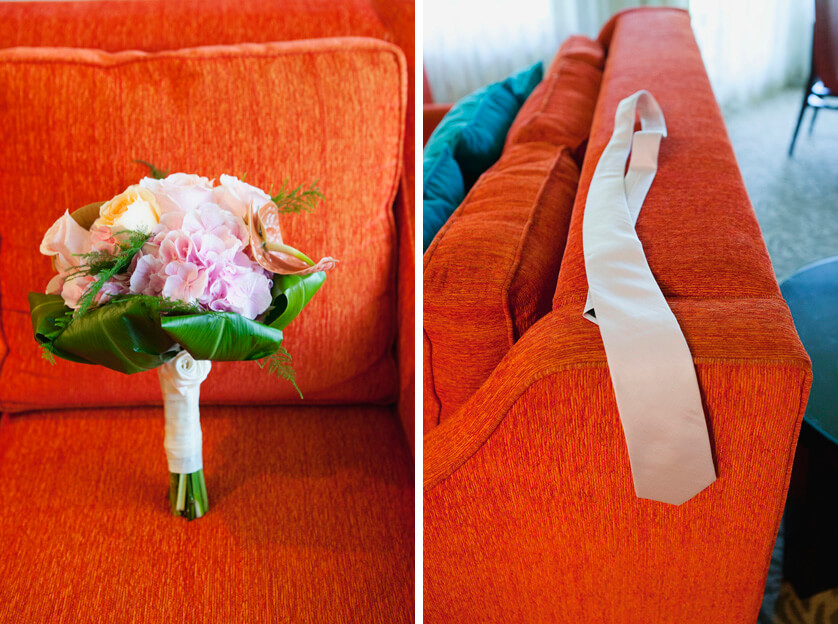 Brides bouquet and grooms tie agains bright orange background