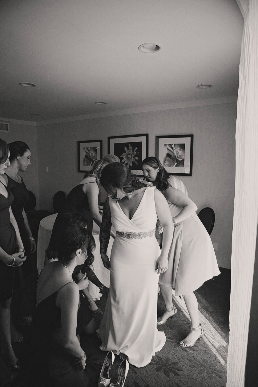 A lovely black and white image of the the bridesmaids helping the bride with her dress