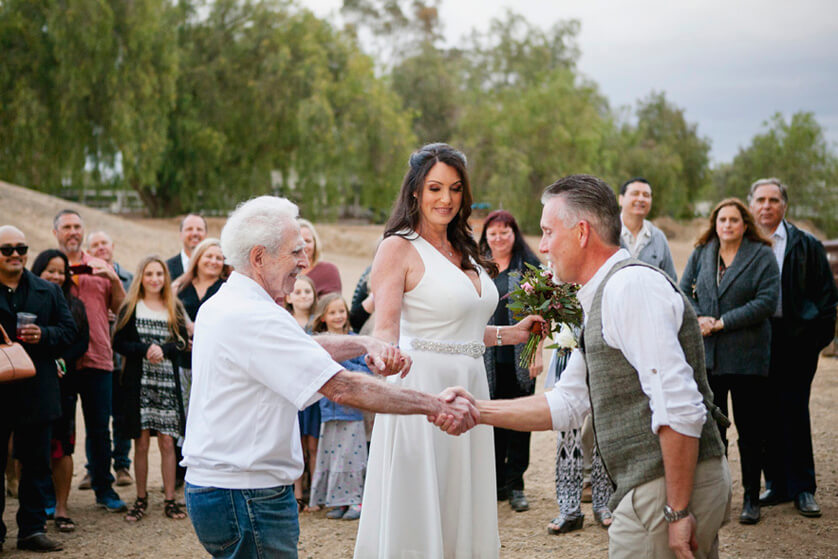 The father of the bride givers the brides hand
