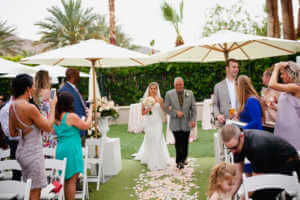 Bride walks down the aisle with here father at this California wedding ceremony in Rancho Mirage